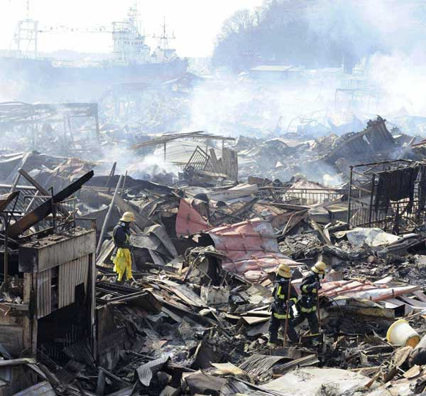 Rescuers conduct search operation amidst smoldering debris in Kesennuma, northern Japan Monday, March 14, 2011 following Friday&#39;s massive earthquake and the ensuing tsunami <span class=meta>( &#40;AP Photo&#47;Yomiuri Shimbun, Miho Ikeya&#41;)</span>
